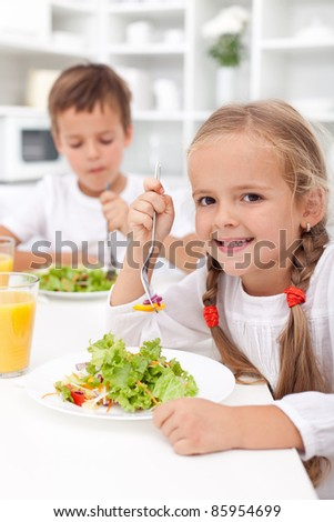Kids in the kitchen eating healthy vegetables - stock photo