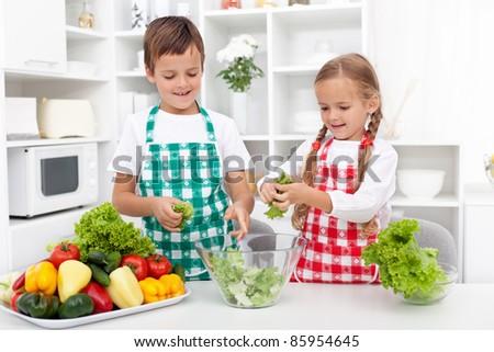 Kids in the kitchen preparing salad - chopping lettuce - stock photo