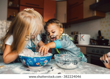 Kids is playing with flour in the kitchen - stock photo