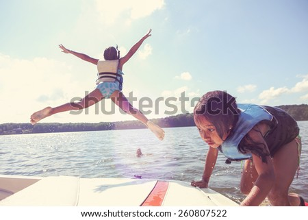 Kids jumping off a boat into the lake. Instagram effect.  Focus on boat and girl  - stock photo