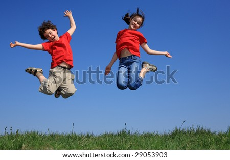 Kids jumping on green meadow - stock photo