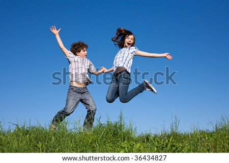 Kids jumping on green meadow against blue sky