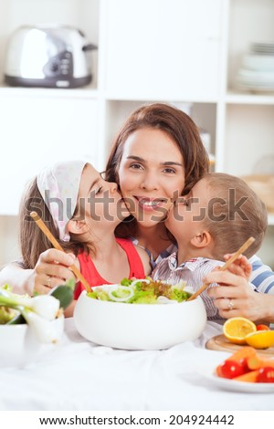 Kids kissing mother in kitchen - stock photo