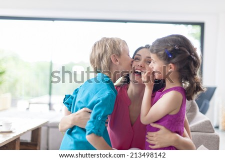 kids kissing their mother on a couch - stock photo