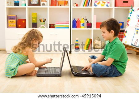 Kids learning and playing computer games sitting on the floor with laptops - stock photo