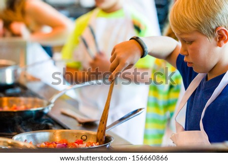 Kids learning how to cook in a cooking class. - stock photo