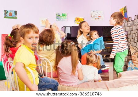 Kids listen to teacher reading book in class
