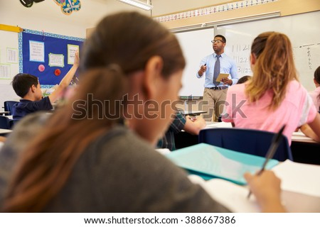 Kids listening to teacher during an elementary school lesson - stock photo
