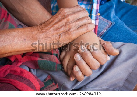 kids little  boy hand touches and holds an old man wrinkled hands. - stock photo
