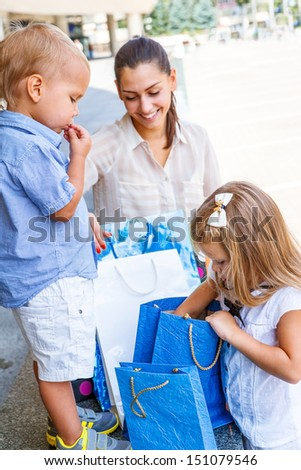 Kids looking into shopping bags beside the mall - stock photo