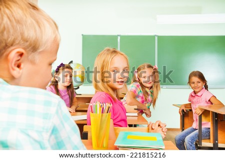 Kids looking straight while sitting at tables rows