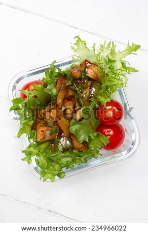 Kids lunch box: lettuce, cherry tomatoes, stewed chicken breast with onions, bell peppers and thyme, sweet chili sauce - stock photo