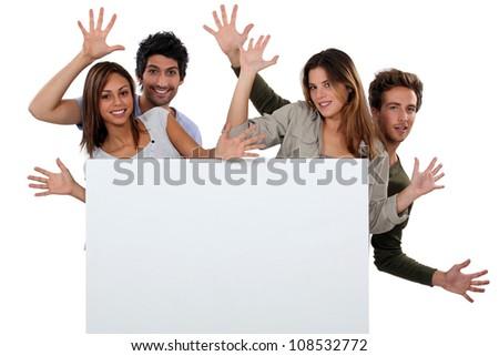 Kids making faces behind white panel - stock photo
