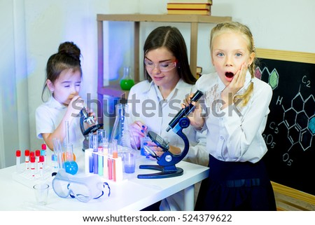 kids making science experiments with their teacher in laboratory. education