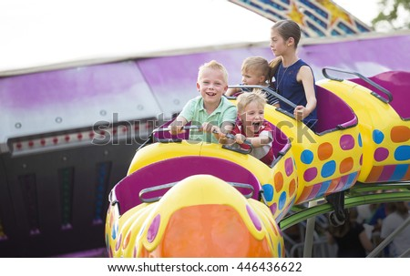 Kids on a thrilling roller coaster ride at an amusement park  - stock photo
