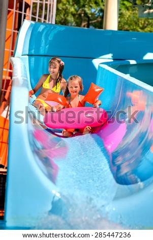 Kids on blue water slide at aquapark. Summer holiday. - stock photo