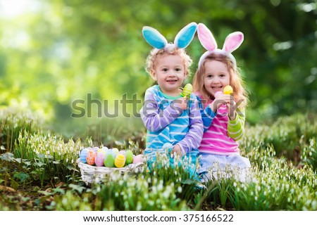 Kids on Easter egg hunt in blooming spring garden. Children with bunny ears searching for colorful eggs in snow drop flower meadow. Toddler boy and preschooler girl in rabbit costume play outdoors.  - stock photo