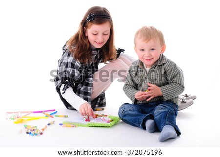 Kids on the floor are painting in notebook
