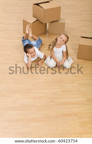Kids on the floor in their new home - top view, copy space - stock photo