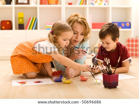 Kids painting hands and making prints with their mother sitting on the floor - stock photo