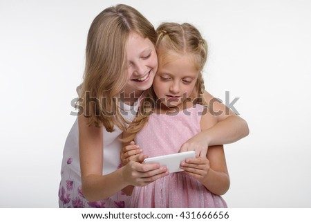 Kids play games on the smartphone as it is very popular nowadays among children and adults. The elder sister embraces her younger sibling and laughs while playing. - stock photo