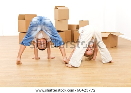 Kids playing and having fun in their new home after moving in - stock photo