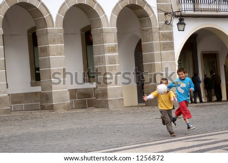 kids playing ball in the street - stock photo
