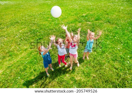 Kids playing ball on a meadow - stock photo