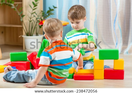 Kids playing block toys in playroom at nursery - stock photo