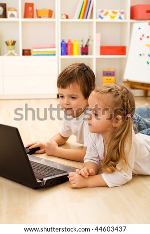 Kids playing computer game on laptop laying on the floor - stock photo