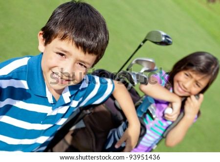 Kids playing golf and holding a bag at the course - stock photo