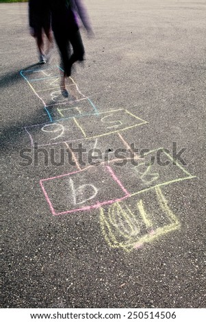 Kids playing hop scotch on the street.