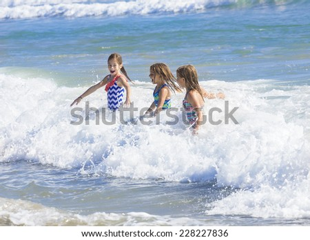 Kids playing in the ocean surf on vacation - stock photo