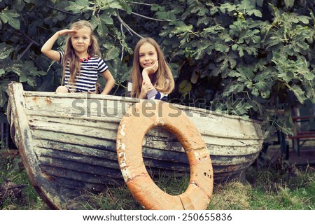 Kids playing inside old boat in summer - stock photo
