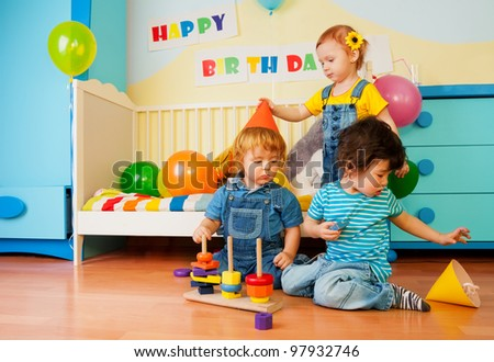 Kids playing on birthday party constructing a pyramid and girl putting on celebration caps - stock photo