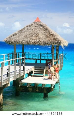 kids playing on pontoon at tropical island - stock photo