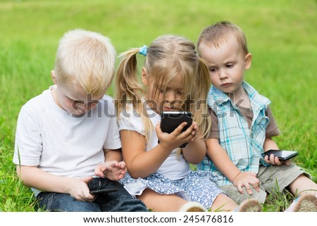 Kids playing on smartphones sitting on the grass in the park. Brothers and sister.  - stock photo
