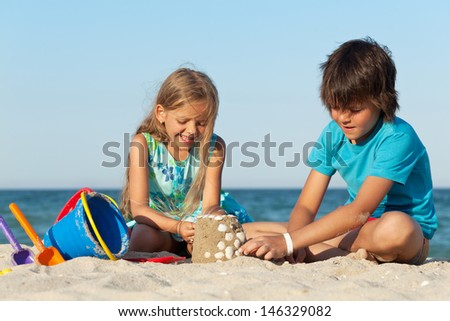Kids playing on the beach building a sand castle decorating it with seashells - stock photo