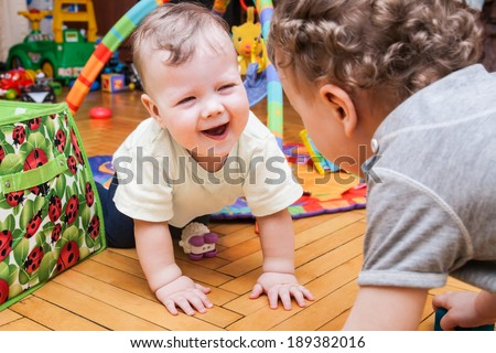 Kids playing on the floor of the childrens room - stock photo