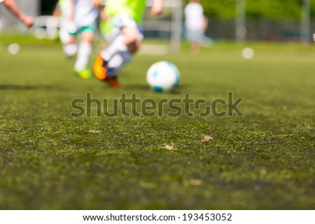Kids playing soccer outdoors on a sunny day. Focus is on the pitch. - stock photo