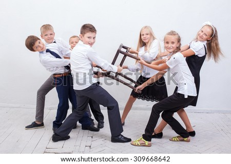 Kids playing tug of chair - girls versus boys on white background. concept of school boys and girls confrontation - stock photo