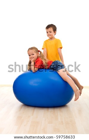 Kids playing with a large exercise ball in the gym - isolated - stock photo