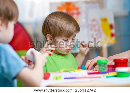 kids playing with play clay at home or  playschool - stock photo