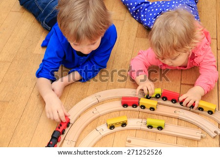 kids playing with railroad and trains indoor, learning and daycare - stock photo