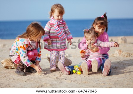 Kids playing with sand at the beach - stock photo