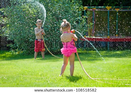 Kids playing with water on a warm summerday in the garden - stock photo