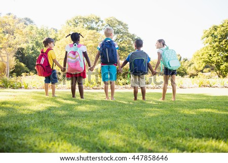 Kids posing together during a sunny day at camera at park - stock photo