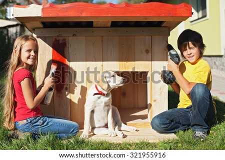 Kids preparing a shelter for their new puppy dog - finishing and painting the doghouse - stock photo