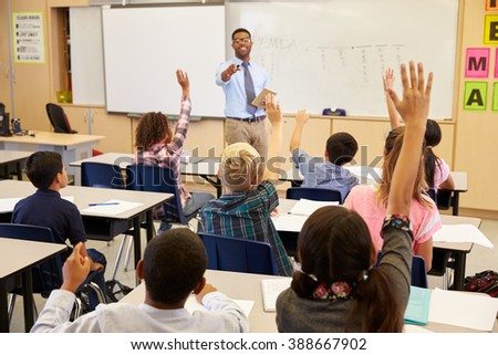 Kids raising hands to answer in an elementary school class - stock photo