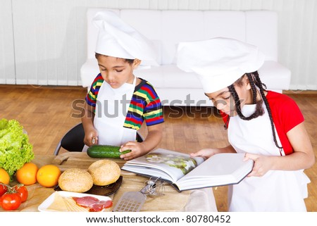 Kids reading cook book and making salad